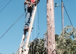 Comcast tech stringing cable on a pole