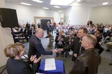 Comcast Regional Senior Vice President Kyle McSlarrow shakes hands after signing the Employer Support of Guard and Reserve document. At right, Eric Barnes of Washington ESGR and Col. Daniel Swain, commander of the 141st Air Refueling Wing, Washington Air National Guard located at Fairchild Air Force Base.